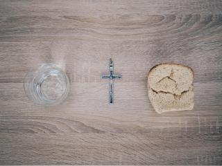 On a table, viewed from above: a cup of water, a silver crucifix, and a torn slice of bread.
