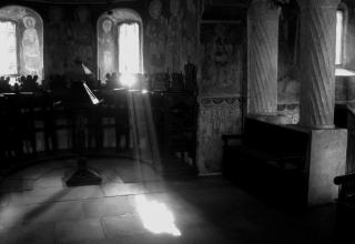 A black and white photo of a sunbeam cutting through the chancel of the Stavropoleos Monastery (Bucharest, Romania)