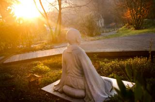 Sunlight shines on a statue of a meditating person..