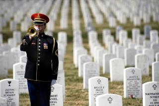 Army soldier in dress uniform playing Taps at Arlington National Cemetery