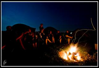 Against an indigo sky, people sit gazing into a sparking campfire.