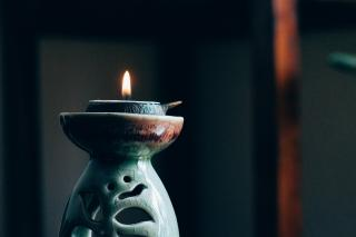 A small flame burns on a ceramic green candle holder