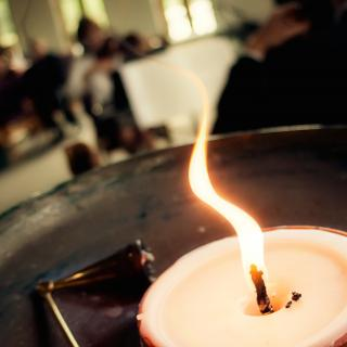 A flame rises from the flaming chalice, a symbol of Unitarian Universalist faith.