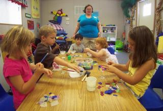 Teacher with young children making chalices.