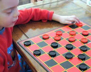 A small child at a checkers board, his arm slung on the table.