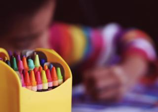 A large box of crayons in the foreground; in the background, a child bent over a drawing