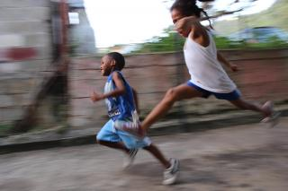 Two children run -- one is mid-jump -- through an alley, smiling.