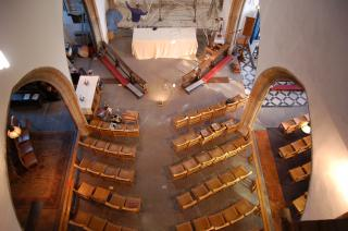 an aerial view of a church nave, with empty seats, undergoing renovation