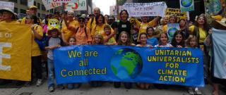 "A multigenerational group, mostly female and mostly white, at a Climate Action march, showing a blue banner with a big image of our planet which says ""UUs for Climate Action"""