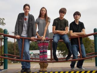 Four young people stand on a bridge to symbolize their transition from childhood to adolescence.