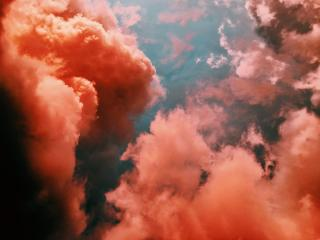 Vivid orange smoke, or clouds, against a background of water or sky.