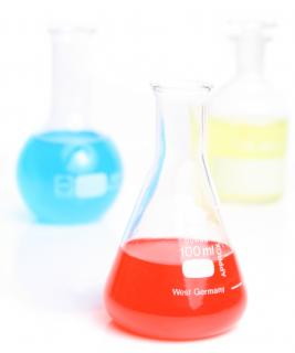 Three laboratory flasks sit on a white counter, each filled with a vividly colored liquid (sky blue, cherry red, and sunshine yellow)