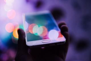 A person holds a smartphone, whose screen reflects colorful lights