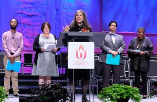 Four people stand in background and one person speaks from podium on stage at GA 2019