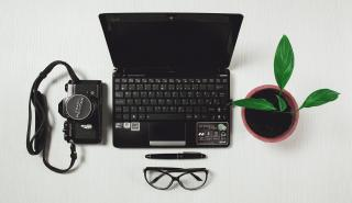An overhead shot of a laptop computer, camera, pen, glasses, and plant.