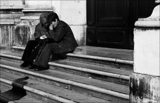 a black-and-white photo of two people, sitting on stone steps. One is comforting the other.