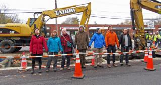 Clergy and others holding hands at a construction site protest.