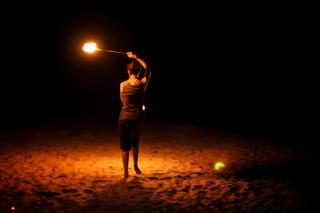"From behind, a lone person spins ""poi,"" or fire baskets, in the dark."