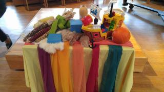 On a church altar rest: ears of corn, a plastic toy ship, and blue grid squares