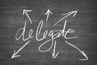"The word ""delegate"" on a chalk board with arrows pointing in all directions"