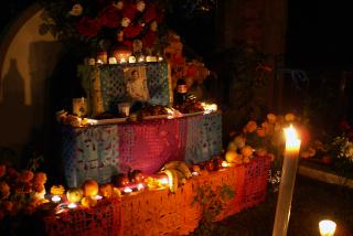 An altar filled with candles, photos, and flowers