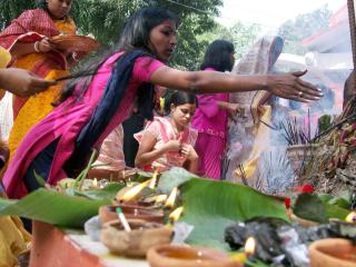 Hindu women at an altar of candles and incense