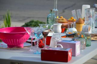 An array of glasses, bowls, and trinkets set on a table for a yard sale.