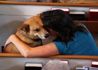 In a church pew, a woman hugs and nuzzles a happy-looking dog