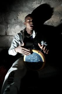 A Black man, with his back against a wall, closes his eyes as he drums.