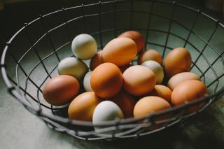 A wire basket with eggs in a range of natural colors