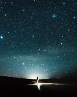 blue_green_night_sky_black_foreground_person_standing_in_light