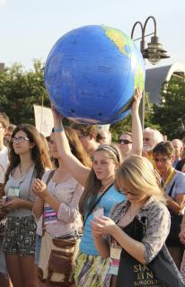 Young woman holds plastic earth ball at rally for environmental justice in Louisville, KY, June 2011.
