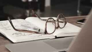 a pair of glasses sits on a notebook with writing