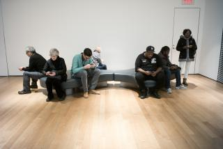 On and around a museum bench, seven different people each bows their head over their respective smartphone.