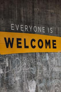 "A message painted on a wall: ""Everyone is Welcome"""