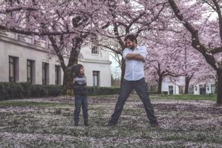 A man and a girl in a yard covered with cherry blossoms