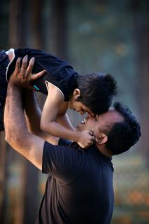 A father and son nuzzle each other; the father looking up, holding his son aloft.