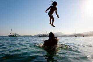 Father in ocean, playfully tossing child.