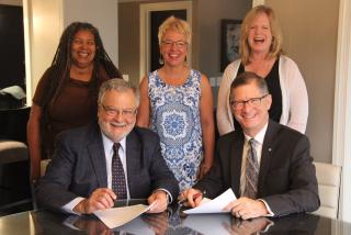 Peter Morales (L) and John Dorhauer, presidents, respectively, of the UUA and the United Church of Christ, backed by staff of both organizations, sign a Memorandum of Understanding to continue partnering on Our Whole Lives sexuality education.