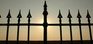 Wrought Iron fence with sunset