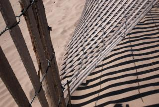 A wooden fence in sand, partially caved in so that it creates entry.