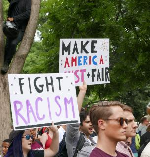 "At an outdoor protest, white people hold signs that say ""Fight Racism"" and ""Make America Just + Fair."""