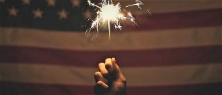 Hand holding a lit firecracker with american flag in the background