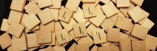 Five letter I Scrabble tiles on a pile of other tiles