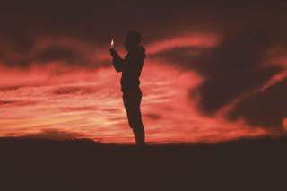 The silhouette of a person holding a lighter (with flame) against a red sky.