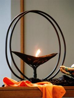 a flame inside of a graceful chalice, on an altar