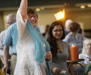 A piece of brightly flaming flash paper hangs suspended in midair as a parishioner, arm lifted, looks on in wonder.