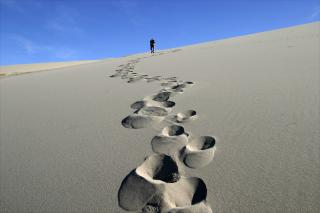 A line of footprints going up a sand dune, leading to a small figure on the horizon