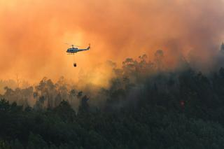 Against a violent orange smoke, a helicopter hovers over a forest on fire.