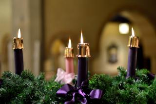 Three purple and one pink candles, all lit, on an Advent wreath